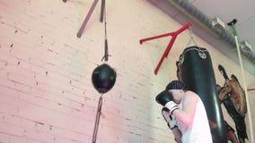 Beautiful kickboxing woman training punching bag in fitness studio fierce strength fit body kickboxer series 4k. Beautiful kickboxing woman training punching bag stock video footage