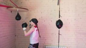 Beautiful Kickboxing woman training punching bag in fitness studio fierce strength fit body kickboxer series 4k stock video