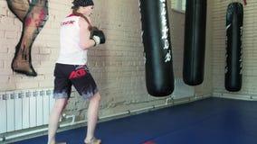 Beautiful Kickboxing woman training punching bag in fitness studio fierce strength fit body kickboxer series 4k stock footage