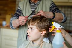 Beautiful kid boy with blond hairs getting his first haircut. Hands of hair stylist cutting curly hairs with scissors. Happy child sitting and waiting Royalty Free Stock Image