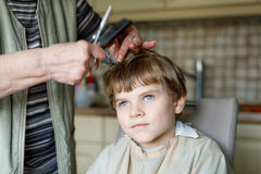 Beautiful kid boy with blond hairs getting his first haircut. Royalty Free Stock Image