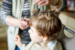 Beautiful kid boy with blond hairs getting his first haircut. Hands of hair stylist cutting curly hairs with scissors. Happy child sitting and waiting Stock Image