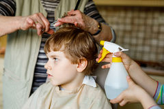 Beautiful kid boy with blond hairs getting his first haircut. Hands of hair stylist cutting curly hairs with scissors. Happy child sitting and waiting Stock Images