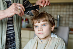 Beautiful kid boy with blond hairs getting his first haircut. Royalty Free Stock Photo