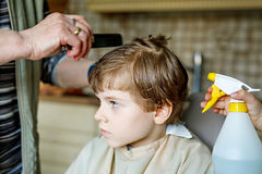 Beautiful kid boy with blond hairs getting his first haircut. Hands of hair stylist cutting curly hairs with scissors. Happy child sitting and waiting Royalty Free Stock Photos