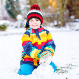 Beautiful kid boy in colorful clothes making a snowman Stock Photography
