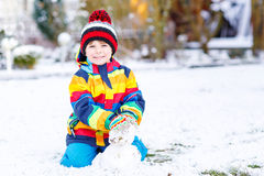 Beautiful kid boy in colorful clothes making a Royalty Free Stock Photos