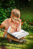Beautiful kid boy with glasses, reading a book in garden, sitting on grass. Stock Images