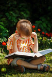 Beautiful kid boy with glasses, reading a book in garden, sitting on grass. Royalty Free Stock Image