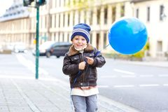 Beautiful kid boy playing with blue air balloon outdoors on street of city. Happy toddler running, walking, smiling and. Laughing. Healthy childr outside on stock photo