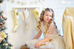 Beautiful kid by the decorated fireplace Royalty Free Stock Photos