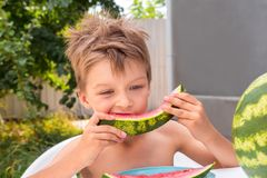 Beautiful kid eating watermelon outside in the garden. Red ripe watermelon eaten by the boy. Healthy food background stock photo