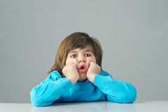 Beautiful kid feeling bored isolated on grey background Stock Image