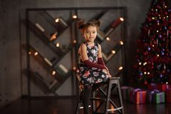 Free Beautiful Kid Girl 5-6 Year Old Wearing Stylish Dress Sitting In Armchair Over Christmas Tree In Room. Looking At Camera. Holiday Royalty Free Stock Photography - 151403167