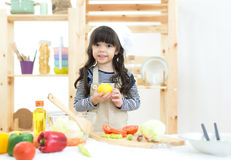 Beautiful kid girl cooking and cutting vegetables. On kitchen Royalty Free Stock Photos