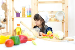 Beautiful kid girl cooking and cutting vegetables. On kitchen Royalty Free Stock Photography