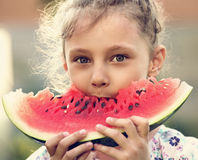 Beautiful kid girl eating big red tasty watermelon with cute loo Stock Photos