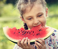 Beautiful kid girl eating big red watermelon with fun emotional Stock Images
