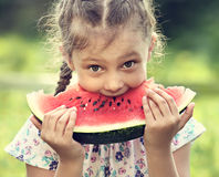 Beautiful kid girl eating big red watermelon with fun humor look. On summer day green glass background. Closeup toned portrait royalty free stock image