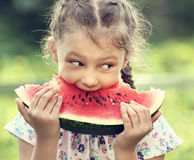 Beautiful kid girl eating big red watermelon on summer day green Royalty Free Stock Image