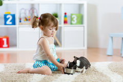 Beautiful kid girl feeding her dog in the living room royalty free stock photography