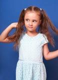 Beautiful kid girl with long hair posing in fashion dress on bri Stock Photos