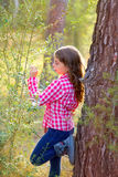 Beautiful kid girl looking plants in forest. Beautiful kid girl profile looking plants in pine forest outdoor royalty free stock photo