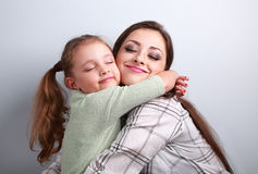 Beautiful kid girl and mother hugging with closed true enjoying Royalty Free Stock Photos