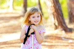 Beautiful kid girl in park forest smiling. With trekking pole royalty free stock photography