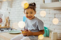 Beautiful kid having morning relax in kitchen. Join me. Charming girl expressing positivity and looking straight at camera royalty free stock photo