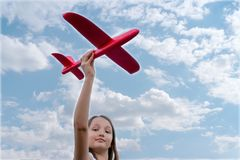 Beautiful  kid holding in hands a red toy airplane on a background of blue sky stock images