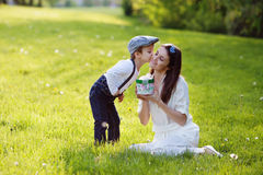 Beautiful kid and mom in spring park, flower and present. Mother Royalty Free Stock Image