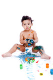 A beautiful kid playing with his paintings Stock Image