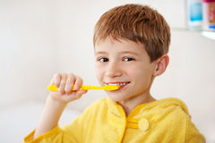 Beautiful kid preparing to brush their teeth wearing yellow bathrobes. closeup. Little boy in bathrobe washing his teeth after evening bath Stock Photos