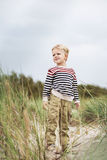 Beautiful kid standing in the dunes and watching something. Oudoor portrait Royalty Free Stock Photos