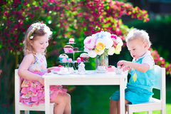 Beautiful kids having fun at garden tea party Stock Photos