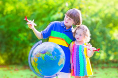 Beautiful kids playing with airplanes and globe. Two happy children, cute curly toddler girl and a smiling school age boy playing with toy airplanes flying over royalty free stock images