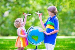 Beautiful kids playing with airplanes and globe Stock Images