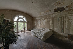 King Master Bed with Arched Windows & Hardwood Floors - Abandoned Mansion. A beautiful king sized bed surrounded by cream colored plastered walls, an arched Stock Photo
