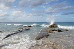Beautiful Kirra Beach. A Sunny day at beautiful Kirra Beach, Queensland, Australia. Captured as a wave splashes onto the rocks Stock Images