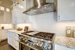 Beautiful kitchen features a nook filled with steel stove stock photo