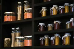 Beautiful kitchen glass jars for storing bulk products on a dark shelf with cereals, pasta, spices and beans stock photos
