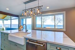 Beautiful kitchen with green island and farm sink. Beautiful kitchen room with green island, farmhouse sink and gorgeous water view royalty free stock image