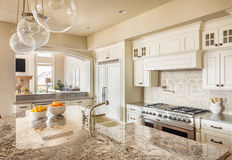 Beautiful Kitchen in Luxury Home. Kitchen with Island, Sink, Cabinets, and Hardwood Floors