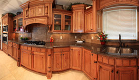 Beautiful kitchen panorama. Panorama of modern kitchen in luxury home includes custom wood cabinets, tile and custom stone countertops Stock Images