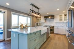 Beautiful kitchen room with green island and farm sink. Beautiful kitchen room with green island and farmhouse sink stock photo