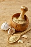 Wooden mortar and pestle with garlic and grind spices on rustic table, close-up, selective focus, vertical. Beautiful kitchen still life wooden mortar full of royalty free stock images
