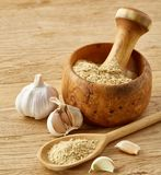 Wooden mortar and pestle with garlic and grind spices on rustic table, close-up, selective focus. Beautiful kitchen still life wooden mortar full of grind royalty free stock photo