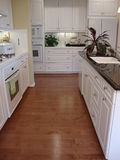 Beautiful Kitchen with Wood Floors. Designer kitchen with white cabinets  and wood floors black granite counters white appliances Royalty Free Stock Photos