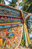 Beautiful Kolae boat, traditional Thai-Malayu fishing boat. Colorful mural painting and color cloth hanging on the bow of the boat. Coconut trees and local royalty free stock photos